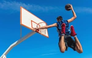 basketball player jumping for a dunk and showing off his basketball shoes