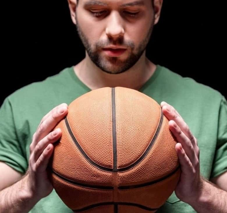 how to clean and care for your basketball: man looking at a basketball